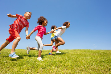 Diverse group of happy kids run in park hold hands