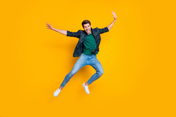 Full size photo of satisfied excited enthusiastic man jump enjoying free time on holidays good-looking wear modern trendy outfit isolated over yellow color background
