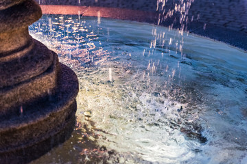 Closeup of splashing water fountain in downtown village park during evening dark night with illuminated light lamps