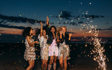 Happy friends celebrating outdoors at sunset. Four stylish women throwing confetti outdoors near fireworks.