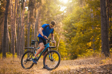 Happy bearded man cyclist rides in the sunny forest on a mountain bike. Adventure travel.