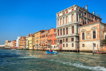 View of Canal Grande. Various boats float by a fine architectural complex of embankments.