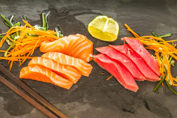Slices of salmon and tuna sashimi sushi on a slate plate with lime and chopsticks
