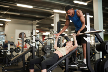 Portrait of African-American fitness coach helping young woman lifting weights on bench in modern gym, copy space