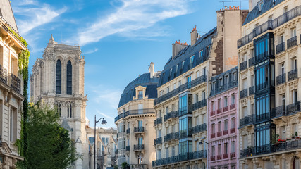 Paris, charming street and buildings, typical parisian facades in the Marais, with Notre-Dame cathedral in background