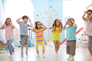 Happy kids having fun dancing indoors in a sunny room at day care or entertainment center