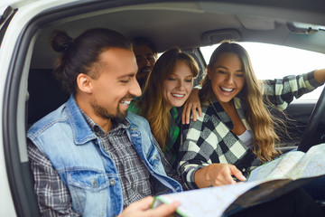 A group of friends choose the route on the map ride in the car.