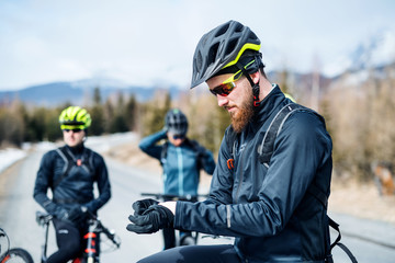 Group of mountain bikers standing on road outdoors in winter.