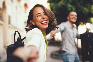Szczęśliwi przyjaciele turyści trzymają się za ręce i przeciągają się przez miasto