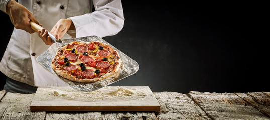 Chef removing a salami pizza from the oven