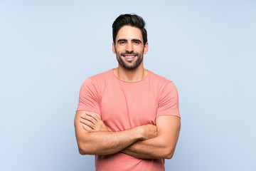 Handsome young man in pink shirt over isolated blue background keeping the arms crossed in frontal position