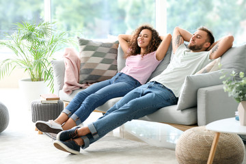 Happy young couple relaxing on sofa at home