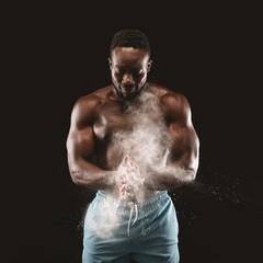 Young black sportsman applying talcum powder on his hands