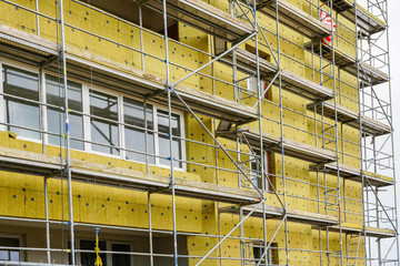 scaffolding arround the house to install thermal insulation of the apartment building facade