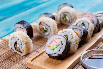 Sushi Rolls in a Row with Salmon, Rice and cucumber on Blue Wood background. White and Black Sushi, Sushi Rolls on Seaweed. Closeup of Delicious Japanese food with Sushi Roll