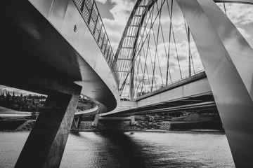 Close-up of suspension bridge over river shot in black and white with clouds and shadows