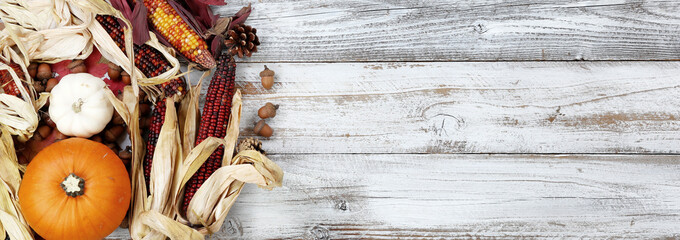 Autumn holiday concept with corn, gourd, pumpkin and acorns on white wood background in overhead view