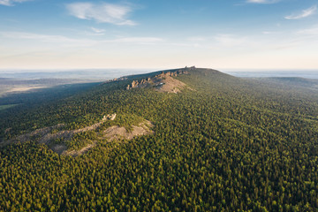 Panoramic aerial view of Ural mountains ridge with Pomyanenny (Kolchimsky) stone among taiga forest on a summer evening. Popular tourist place near Krasnovishersk, Perm krai, Russia.