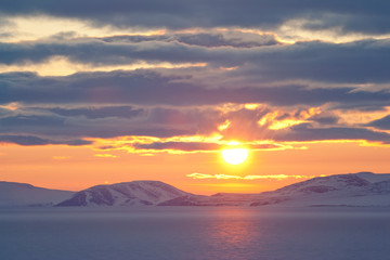 Midnight sun in spring in the Arctic. At the end of May, on the coast of the Arctic Ocean, the sun does not go beyond the horizon all night. East Siberian Sea, Chukotka, Russia. Polar region.
