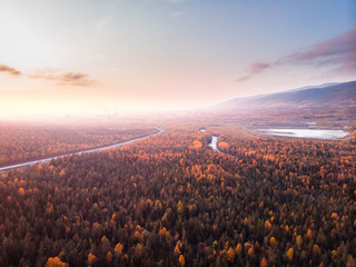 Beautiful autumn forest with yellow and red trees, blue mountain river sunset, aerial view