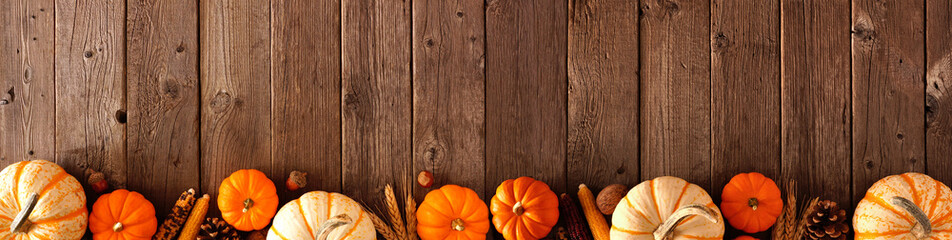 Autumn bottom border banner of pumpkins and fall decor on a rustic wood background with copy space