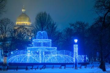 Świąteczny Sankt Petersburg. Rosja. Widok miasta na Boże Narodzenie. Fontanna świateł na placu Świętego Izaaka. Fontanna ozdobiona jest girlandami. Światła wieczornego miasta. Katedra Izaakiewskiego.