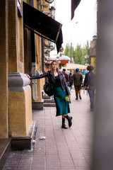 Young beautiful woman walks around the city in Europe, street photo, female posing in the city center