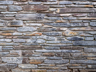 Natural stone wall with stones in various sizes, colors and shades