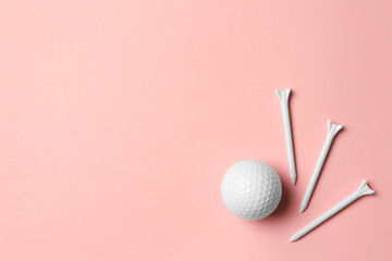 Golf ball and tees on pink background, flat lay. Space for text