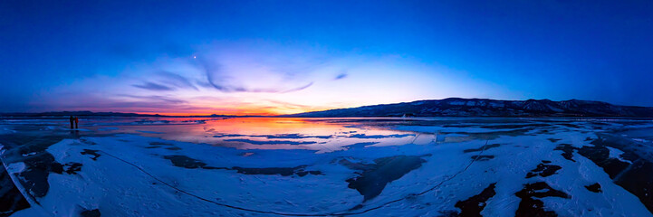 colorful sunset on winter crack ice lake Baikal . Wide panorama