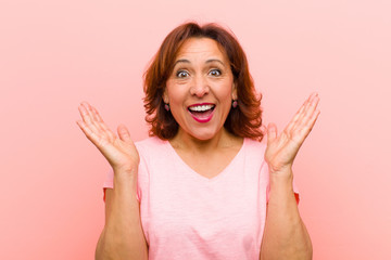 middle age woman looking happy and excited, shocked with an unexpected surprise with both hands open next to face against pink wall