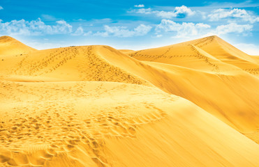 Desert with sand dunes and clouds on blue sky. Landscape of natural reserve Maspalomas Dunes. Gran Canaria, Spain