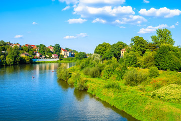 View of Vistula river with houses in background on sunny summer day, Krakow, Poland