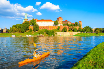 Unidentified young woman paddling in yellow kayak on Vistula river with Wawel castle in background, Krakow, Poland