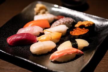 Assorted sushi set served on black tray.