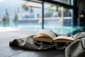 Book lying on a towel beside an indoor swimming pool with blue water, travel, relaxing & reading