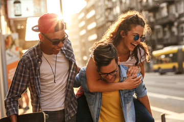 Group of friends hangout at the city street.They embrace each other and laughing.One man carrying female friend on his back.