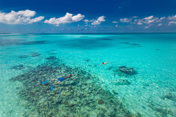 Couple snorkeling over coral reef in Maldives. Luxury summer travel and vacation concept banner. Beautiful tropical nature environment