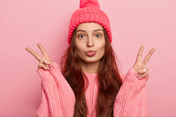 Young beautiful brunette European woman keeps lips rounded, makes victory peace gesture, wears knitted hat and oversized sweater, has long hair, ready for winter walk, isolated over pink background.