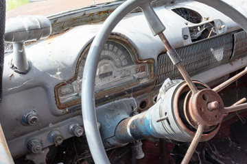 Steering wheel of an old abandoned rusty car with a speedometer close up