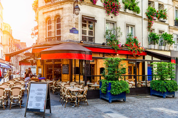 Cozy street with tables of cafe in Paris, France. Architecture and landmark of Paris. Cozy Paris cityscape.