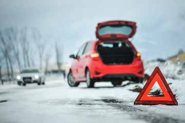 Car red triangle in winter. Emergency sign. Broken car on highway. Warning triangle on snow after car breakdown.