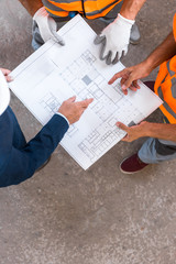 cropped view of constructors and businessman standing and holding blueprint