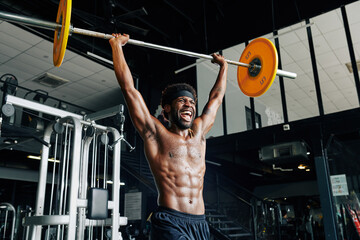 Fit sweaty Black man shouting when lifting heavy barbell high above his head
