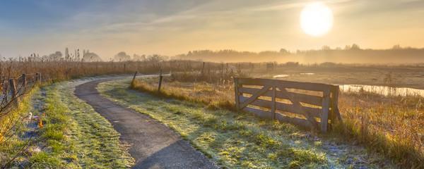 Gate in misty agricultural landscape