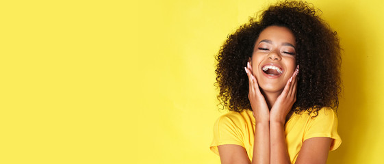 Super happy afro-american girl isolated on yellow background.