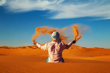 Single Man throws sand in the Sahara desert at sunset.