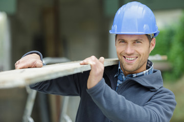 happy contractor in hard hat holding plank of wood