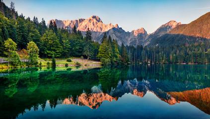 Spokojny poranek widok na jezioro Fusine. Kolorowy lato wschód słońca w Juliańskich Alps z Mangart szczytem na tle, prowincja Udine, Włochy, Europa. Piękno natury pojęcia tło.
