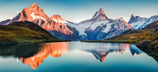 Fantastic evening panorama of Bachalp lake / Bachalpsee, Switzerland. Picturesque autumn sunset in Swiss alps, Grindelwald, Bernese Oberland, Europe. Beauty of nature concept background..